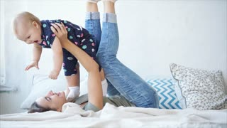 Mother and little kid are having good time together in room of their home. Woman is lying on a bed and lifting baby over her head, they are laughing and joying.