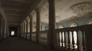 Moving shot in old dilapidated building. Showing empty long tunnel, columns and ceiling with peeling paint