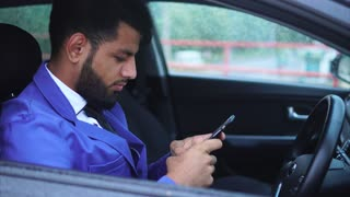 Muslim businessman sitting in the driver's seat in the car and typing on the smartphone. Arab man nowadays.