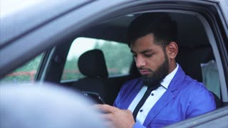 Muslim man sitting in the driver's seat in the car and typing on the smartphone. Arab man in our days.