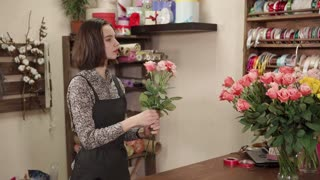 Nice brunette girl with short hairs taking flowers out of vase indoor. She is making a rose bouquet.