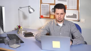 Office worker at work. Man sitting at the desk and using laptop. Classical office environment.