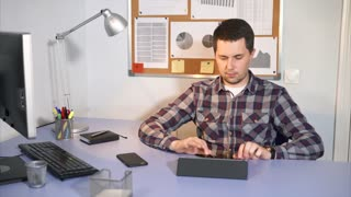 Office worker checks incoming mail on the tablet in his personal account sits at the table in his office. The man uses a touch screen to connect to the Internet.