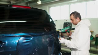 One skilled in the body shop applies a vinyl surface to the vehicle and gradually smoothing squeegee film pastes. Need to remove all air bubbles, which are formed under the film.