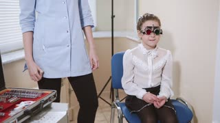 Ophthalmologist is checking the eyesight of a young girl. She is wearing phoropter with different lenses. Testing eyesight.