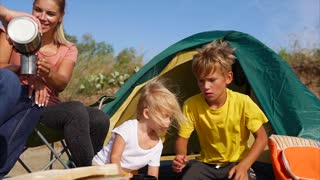 Outdoor family leisure. Parents and kids having a picnic and they are going to stay overnight in a tent. Camping in the countryside