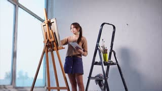 Painter is working on her piece in the art studio with white walls. She is drawing on an easel, there is an art supplies laying close to her.