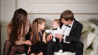 Parents and kids in their best clothes in holiday evening. Happy mom, dad, daughter and baby son sitting on the sofa