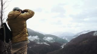 Photo artist is shooting landscape with mountains and river in a fall morning. He is standing on hill and looking in an camera lens, back view