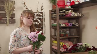 Portrait of a charming blonde woman working with flowers indoor. She is assembling a beautiful bouquet.