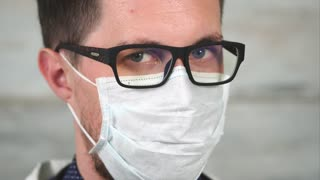 Portrait of a middle-aged man who wears glasses due to poor vision and a rag mask on his mouth, perhaps this is the face of a doctor