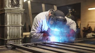 portrait of a professional master in a protective helmet that covers his eyes, the worker is engaged in welding metal sticks in a modern workshop