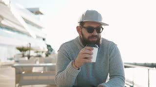 Portrait of a stylish man sitting on a outdoor terrace on the beach alone. He is drinking coffee from paper cup.