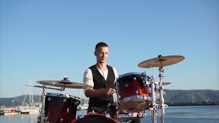 Portrait of a young and enthusiastic musician who plays percussion instruments, a gentleman uses a drum set-up to produce music in the daytime near the sea