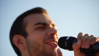 portrait of a young man who sings a song from the outside, a professional singer opens his mouth to music in the daytime on the street, hand of person holding a microphone