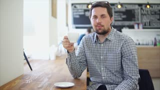 Portrait of a young man with a beard who holds a cup with hot tea or fragrant coffee in a small city cafe, the person sits at a wooden table inside