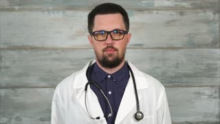 Portrait of adult male doctor with stethoscope in white coat and glasses. Concept of different professions.