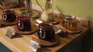 Pots with berry marmalade placed on a table. Camera is panning part of continental breakfast .