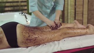 Preparation of the girl's body to the coffee wrap in the spa, the masseur puts cream granules on the legs of the girl. Scrabbing helps remove dead skin from the body to make it younger and softer.