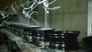 Prepared metal discs are painted in paint shop on a conveyor belt. Plant of producing steel wheels for different vehicles.