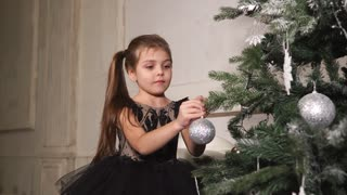 Preschooler girl is dressing Christmas tree, putting on a brilliant ball. She is playing with decoration, twisting it on a branch of spruce, smiling broadly.