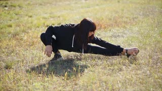 Pretty athletic girl is training outdoors in autumn day, tensioning her legs and squatting. Preparing of sportsmen for competition and championships