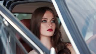 Pretty brunette girl with red lips is inside a car in a seat. Close-up of her face from outside through open door in daytime.
