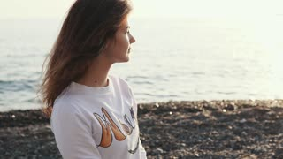 Pretty girl is sitting on pebble coast of sea in sunset time. Close-up of her face, her dark hair is swaying by wind