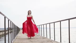 Pretty girl is wearing silk red dress is running on a wooden pier. She is holding her swaying skirt and looking forward, romantic and fashion shot