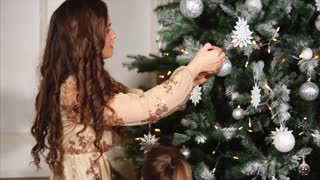 Pretty young woman and man are dressing a Xmas tree, their kids are helping. They are hanging brilliant balls on branches of spruce, camera is moving