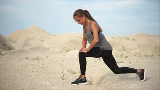 Pretty young woman exercising at one with nature. Girl doing sports among the hills when light wind blowing against her