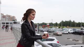 Pretty young woman with dreamy look. She holding hot coffee cup in hands and staring at the city