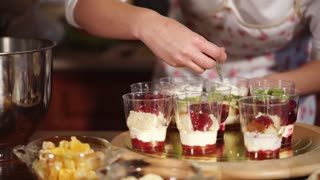 Process of cooking fast dessert for friends and family. Woman is smearing fruits with white cream in cups.