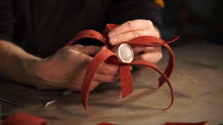 Process of work of a professional leatherworker in studio. He carefully covers tube with red braided leather stripes.