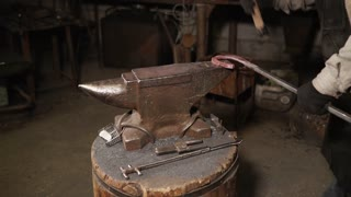 Professional blacksmith puts piece of metal on an anvil and hits with a hammer while it is hot. He hits from every side.