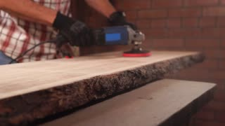 Professional carpenter is working with grinding machine on a piece of wood. He is wearing gloves for protection.