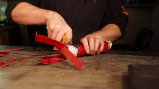 Professional works on a table with a knife on a new accessory. He cuts excess piece of leather off the accessory.