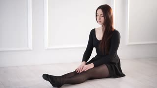 Pupil of a dance school is warming up her ankle joints. She is placing on a floor in hall and moving feet to body and against