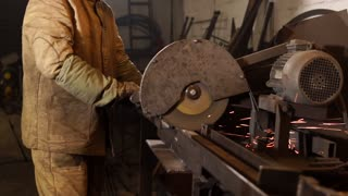 Qualified industrial worker is working on manual grinder to cut different metal tubes. Wheel is spinning and sparks are popping off.