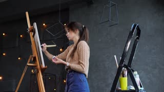 Quite a skilfull artist is drawing a picture on an easel in art studio with black walls. She is painting with a brush very fast.