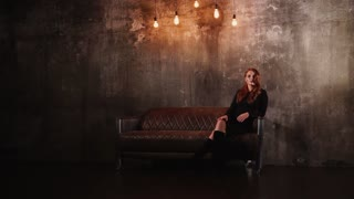 Redhead girl is crossing legs and posing, looking to camera. She is in a luxury leather couch, standing in a dark living room