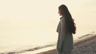 Resting girl with long dark hair is looking on sea waves in evening time. She is approaching to water, jumping over stones , against the sun