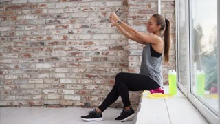 Resting woman takes selfie after hard work out. She sits by the window and takes photos on the smartphone.