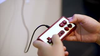 Retro classic gamepad and hands of player. Player pressing buttons and playing in video game. Close up view