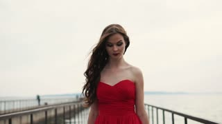 Romantic girl is wearing glamourous red silk gown is moving over old picturesque pier. She is holding flying skirt, little smiling and looking to sides, wind is blowing