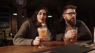 ROSA KHUTOR - FEBRUARY 2018: BAR Portrait of two lovers enjoying their evening at the bar. Drinking exotical cocktails leaning on a wooden bar counter.