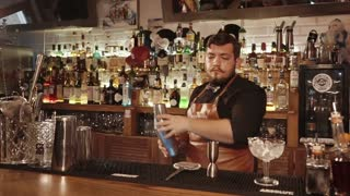 ROSA KHUTOR - FEBRUARY 2018: BAR Skillful bartender mixing drinks in a stainless shaker in the bar. Professional at his job. Pouring his mix.