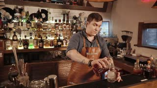 Rosa Khutor, RUSSIA - FEB, 2018: barman is filling crystal glass by alcohol drink. He is rotating glass with ice inside, then he is drinking cocktail and welcoming to camera
