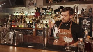 Rosa Khutor, RUSSIA - FEB, 2018: barman is measuring spirit drink by shot and filling shaker. He is preparing a mixed drink for customers of night club