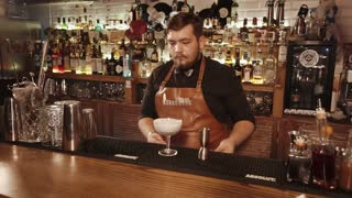 Rosa Khutor, RUSSIA - FEB, 2018: barman is putting paper decor on edge of glass with white alcohol drink. He is moving it forward to client on a wooden round board
